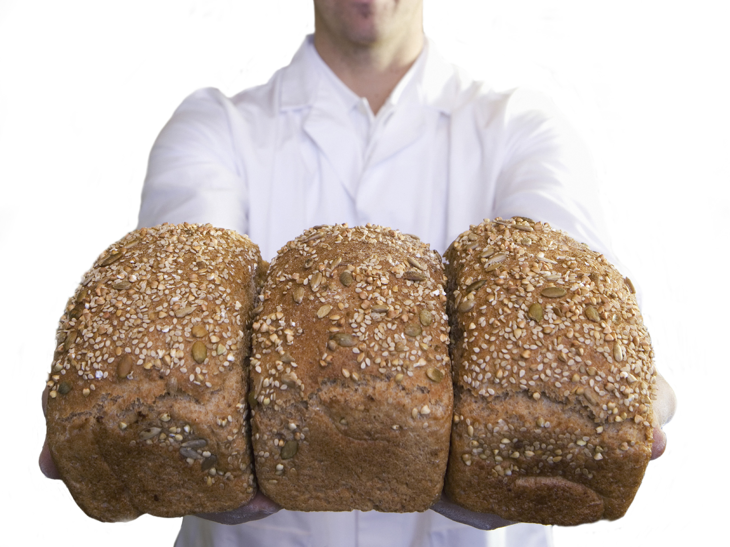 Baker holding fresh bread loaves, cut out