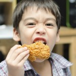 Little boy eating fried chicken