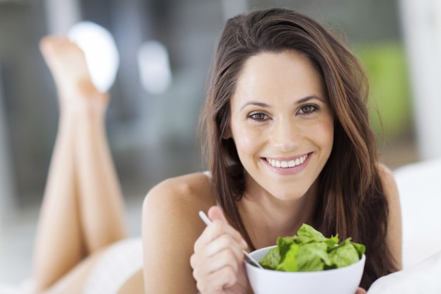 happy young woman eating salad on bed